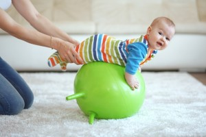 Baby playing with gymnastic ball with mother at home